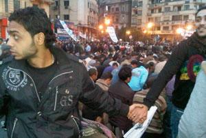 Christian Egyptians guarding Muslims in prayer--Tahrir Square, Cairo